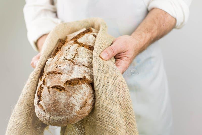 Świeżo piec chleb od piekarza Piekarnianego mienia świeży chleb w rękach obrazy stock