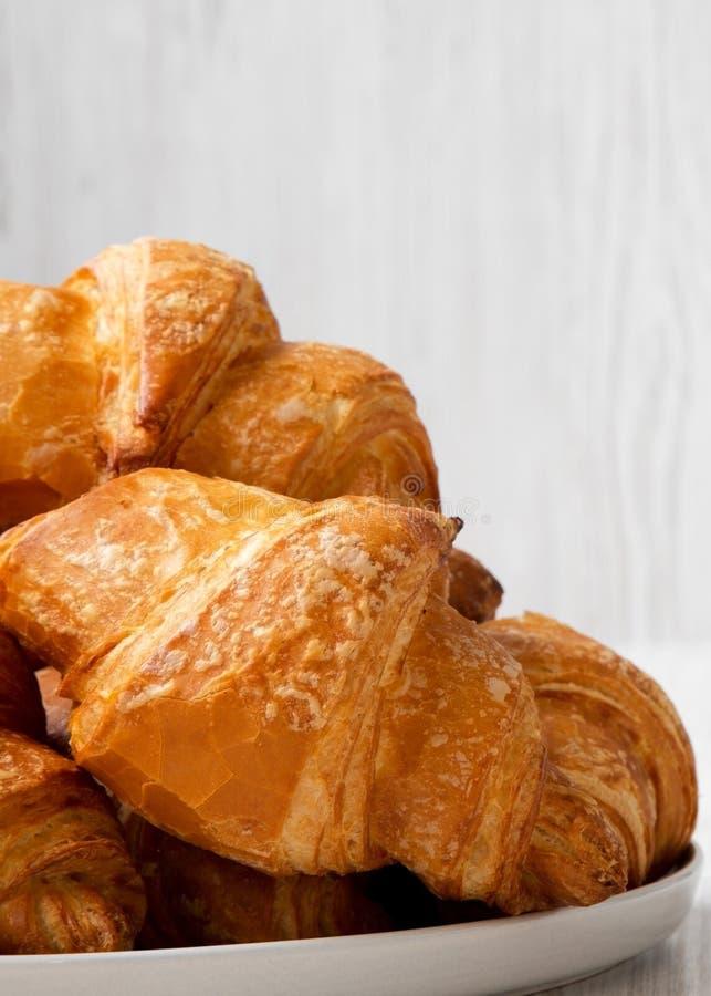 Świeżo piec croissants na round talerzu nad białą drewnianą powierzchnią, boczny widok Zako?czenie zdjęcia royalty free