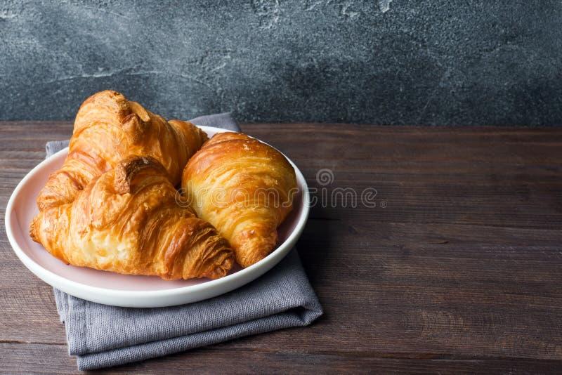 Świeżo piec croissants na talerzu, ciemny tło, kopii przestrzeń obrazy stock