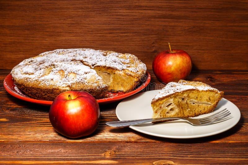 Świeżo piec jabłczany kulebiak na nieociosanym tle ciemny drewno Świezi jabłka i kawałek kropiący z sproszkowanym cukierem o jabł zdjęcie royalty free
