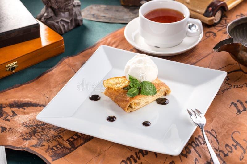Świeżo piec jabłczany strudel z waniliowym lody, mennica i filiżanka herbata na starym mapy tle zdjęcia royalty free
