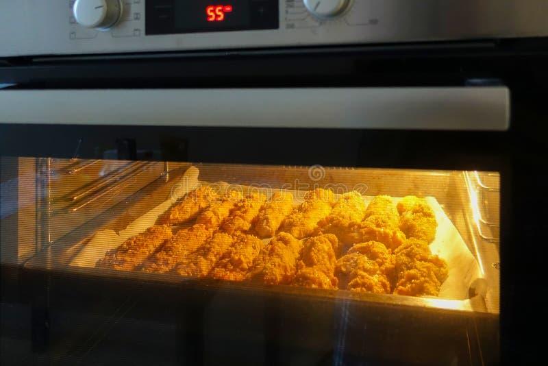 Świeżo piec kurczak polędwicowy na wypiekowym prześcieradle w elektrycznym piekarniku Kulinarne kurczak bryłki serifs obrazy royalty free