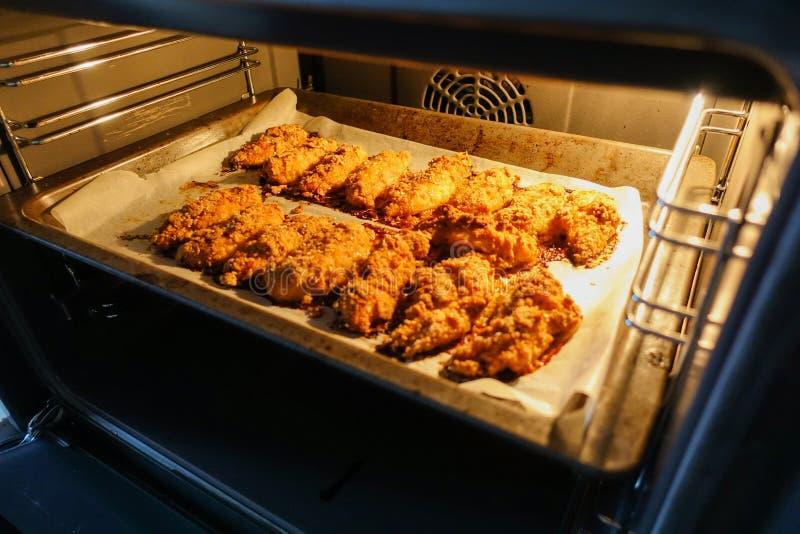 Świeżo piec kurczak polędwicowy na wypiekowym prześcieradle w elektrycznym piekarniku Kulinarne kurczak bryłki serifs zdjęcia royalty free