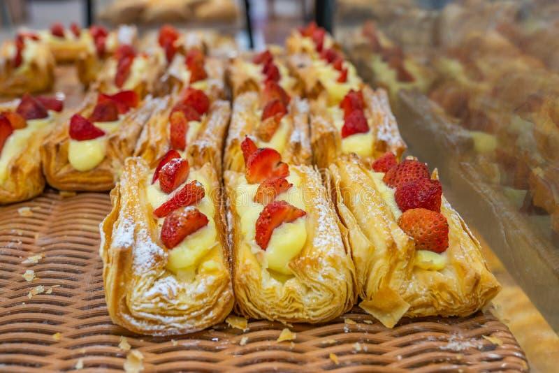 Świeżo piec ptysiowego ciasta i cukierki truskawkowa polewa przy patisserie obrazy royalty free