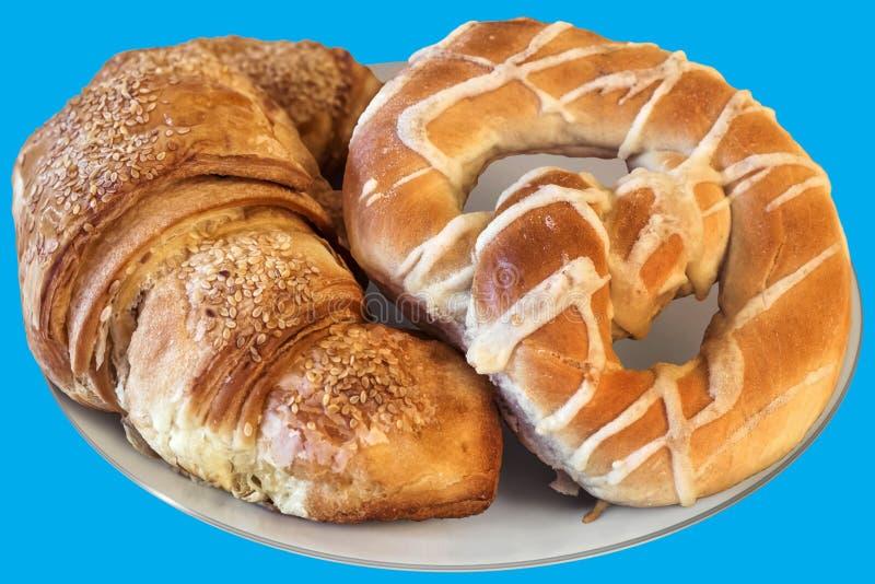Świeżo Piec Sezamowego Croissant Ptysiowy ciasto I precel Słuzyć Na bielu talerzu Odizolowywającym Na Błękitnym tle zdjęcia royalty free