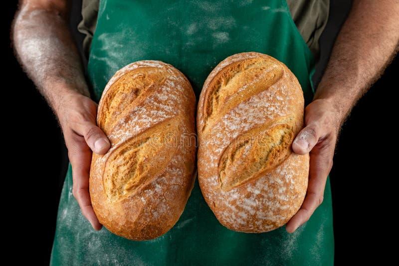 Świeżo piec smakowity chleb w baker& x27; s ręki Smakowity piec towarowy od piekarni prosto fotografia stock