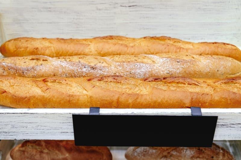 Świeżo piec swobodnie glutenu baguette chleby na białych drewnianych półkach obraz royalty free