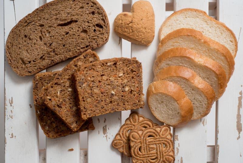 Świeżo piec wyśmienicie chleb na nieociosanym drewnianym worktop z kopii przestrzenią, zdrowy łasowania pojęcie, mieszkanie nieat obraz royalty free