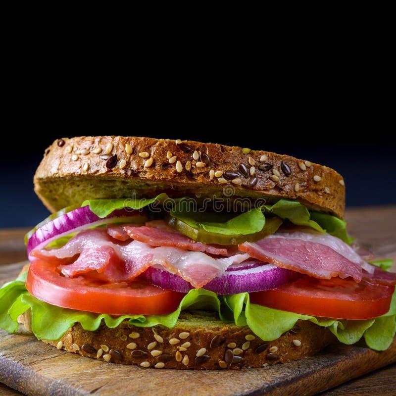 Świeżo przygotowana kanapka z bekonem, pomidor, ogórek, cebula na drewnianej tnącej desce obrazy royalty free