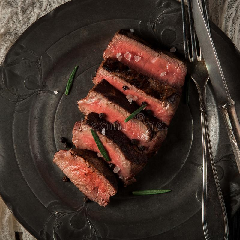 Świeżo przygotowana wołowiny polędwica na ciemnym rocznika talerzu zdjęcia stock