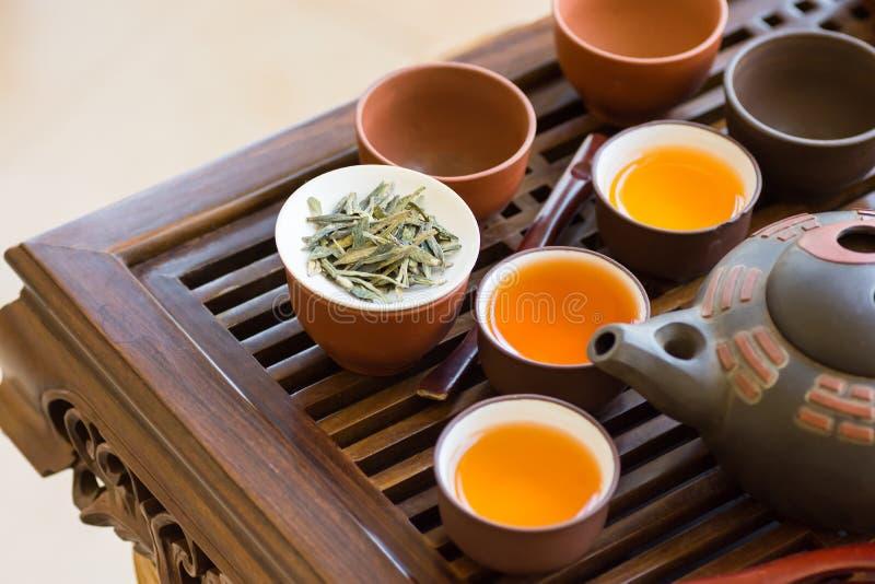 Świeżo warzyć herbaciane nalewać wewnątrz ceramiczne filiżanki puszkują naczynia na drewnianej bambusowej kapiącej tacy Luźni liś obrazy stock
