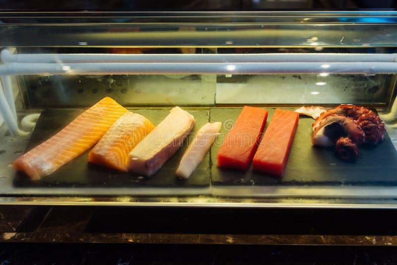 Świeży łosoś, makrela, błękitny żebro tuńczyk i kałamarnica wśrodku chłodziarki która przygotowywa dla robić suszi, obrazy stock