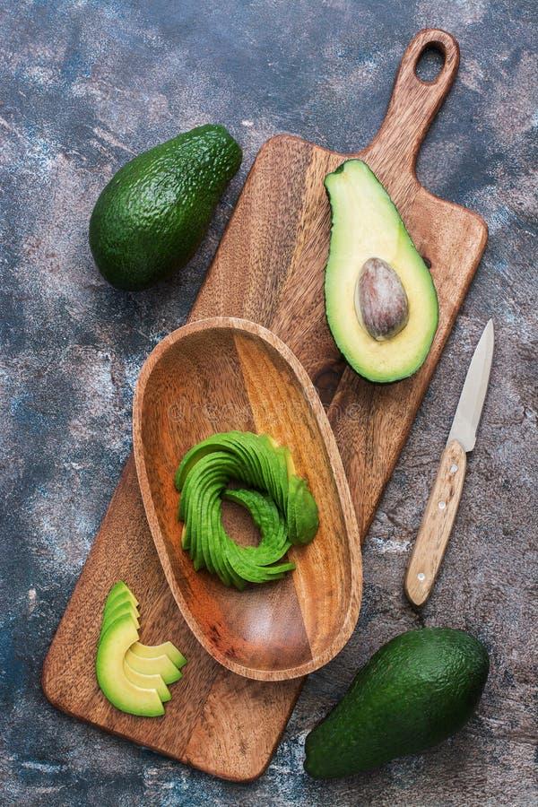 Świeży avocado pokrajać w drewnianym pucharze na tnącej desce na widok zdjęcia royalty free
