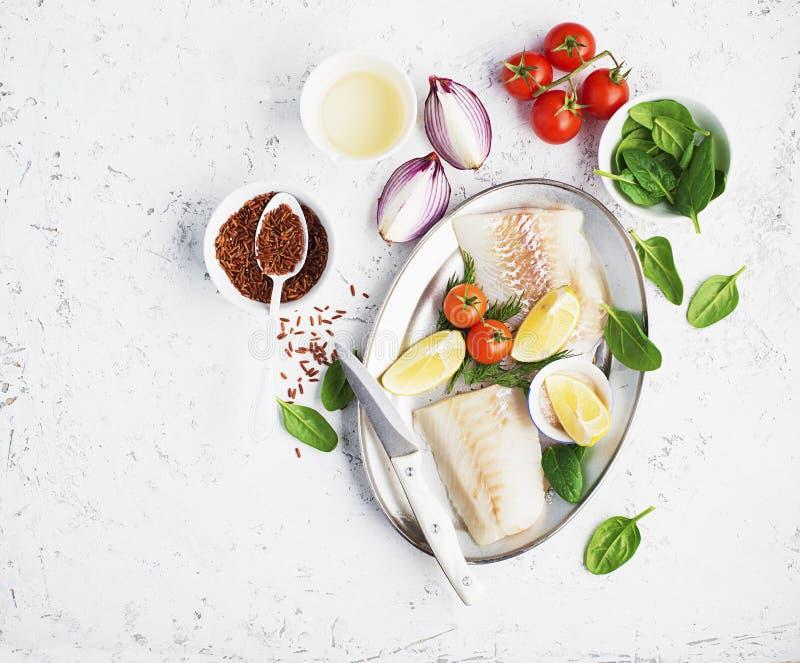 Świeży biały dennej ryba dorsz przepasuje na tle z cebulami, pomidory, czerwoni ryż, sól, szpinak, składniki dla gotować fotografia stock