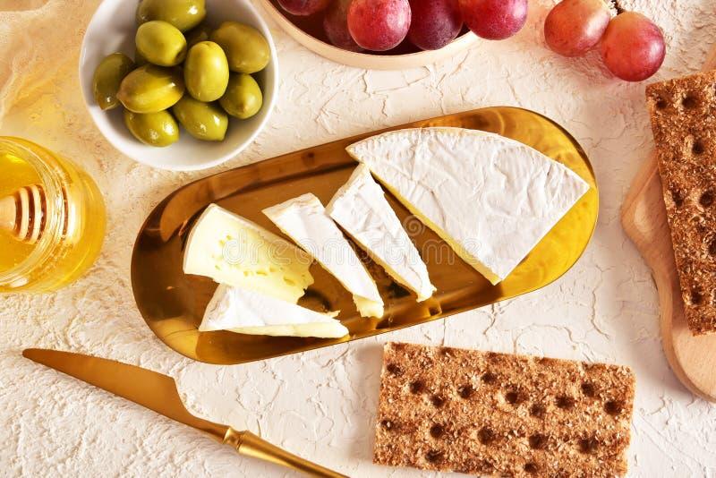 Świeży brie ser na złotym spodeczku Winogrona, miód i oliwki, Odgórny widok fotografia royalty free