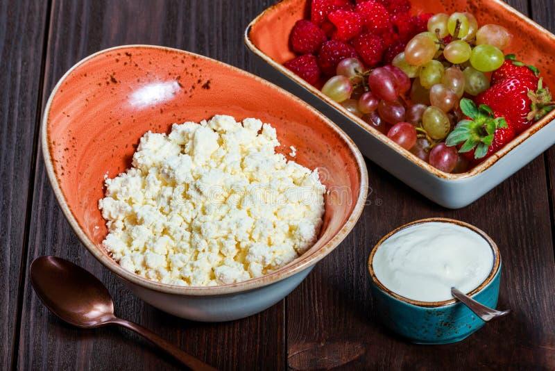 Świeży chałupa ser z soczystymi jagod malinkami, truskawką i winogronami na ciemnym drewnianym tle, zdjęcie stock