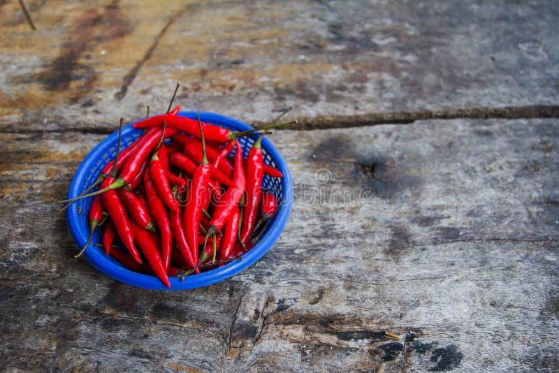 Świeży chili jako składnik w kucharstwie korzenny Układający w koszu umieszczającym na drewnianej podłoga fotografia stock