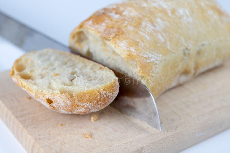 Świeży chleb na drewnianej kuchni desce Plasterek mażący z masłem chleb zdjęcia stock