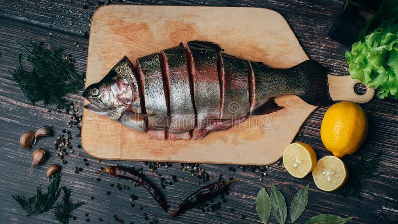 Świeży czerwieni ryby cięcie w kawałki na na pokładzie stołu Pstrąg w kuchni zdjęcia stock
