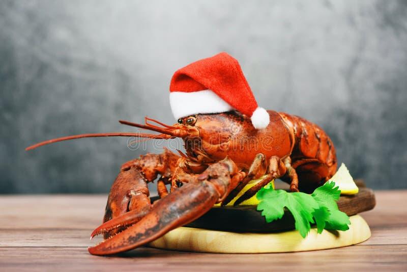 Świeży czerwony homar z świąteczną kapeluszem gotowany w restauracji z owocami morza - obiad z homara na parze na obiad na drewni zdjęcie stock
