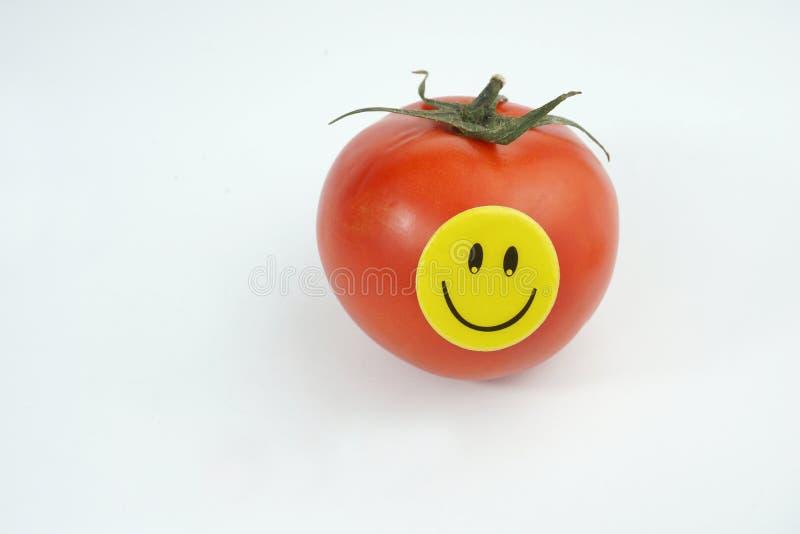 Świeży czerwony pomidor z smiley szczęśliwą twarzą odizolowywającą na białym tle zdjęcia royalty free