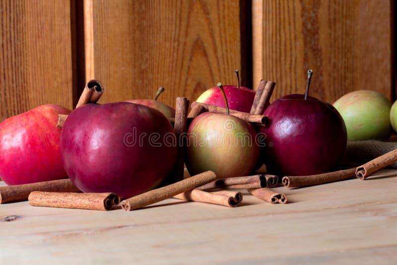 Świeży dojrzały czerwony jabłko i cynamonowi kije na drewnianym tle fotografia stock