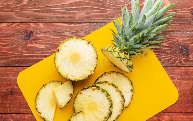 Świeży dojrzały tropikalny ananasa cięcie w plasterki na żółtym rackside lying on the beach na drewnianym stole obrazy stock