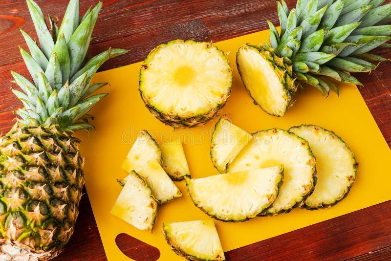 Świeży dojrzały tropikalny ananasa cięcie w plasterki na żółtym rackside lying on the beach na drewnianym stole zdjęcie royalty free