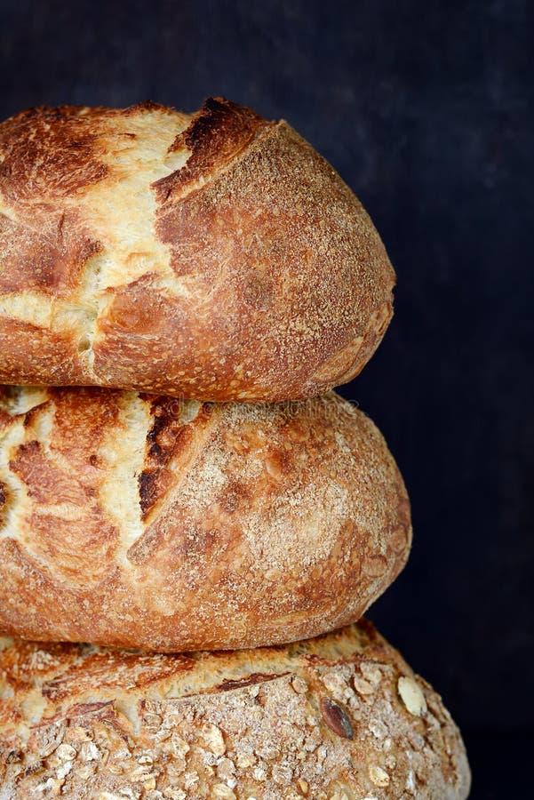 Świeży domowej roboty chleb od całej banatki i żyta mąki z lnów ziaren, bani i owsa płatkami na brown tle, chips obraz royalty free