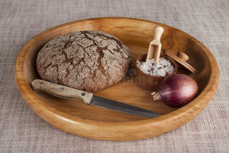 Świeży domowej roboty chleb robić z słojem sól, nóż i cebula, fotografia stock