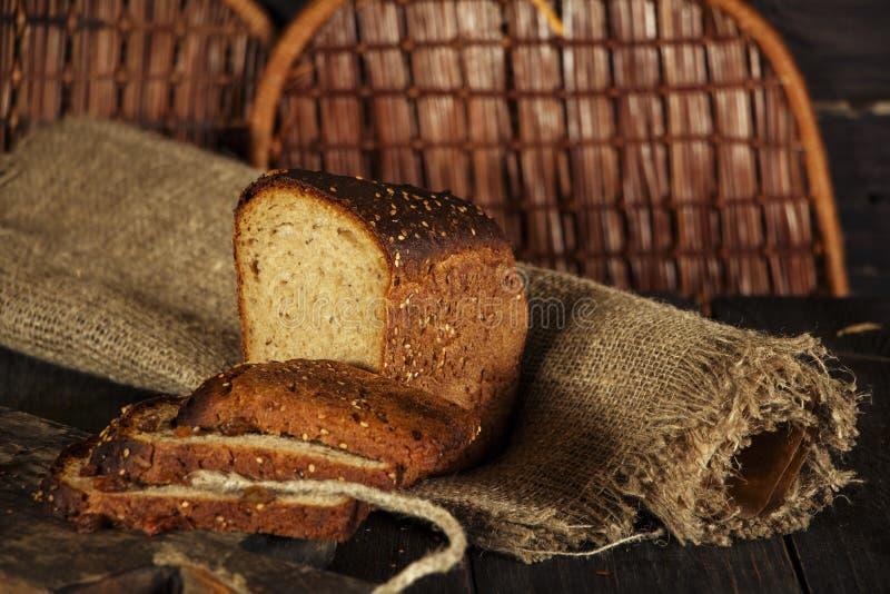 Świeży domowej roboty chleb z całym pszenicznym kolcem na czarnym drewnianym tle Świeży chleb z ucho banatka zdjęcie royalty free
