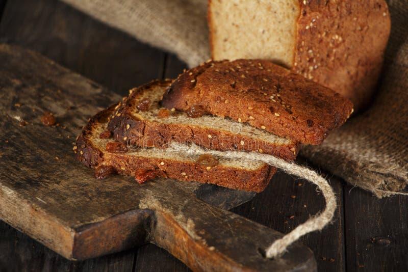 Świeży domowej roboty chleb z całym pszenicznym kolcem na czarnym drewnianym tle Świeży chleb z ucho banatka fotografia royalty free