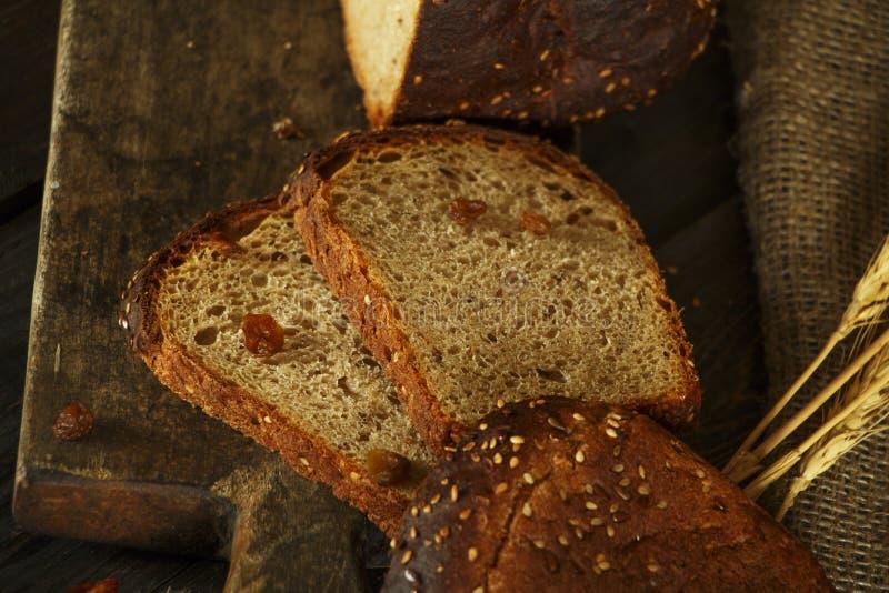 Świeży domowej roboty chleb z całym pszenicznym kolcem na czarnym drewnianym tle Świeży chleb z ucho banatka zdjęcie stock