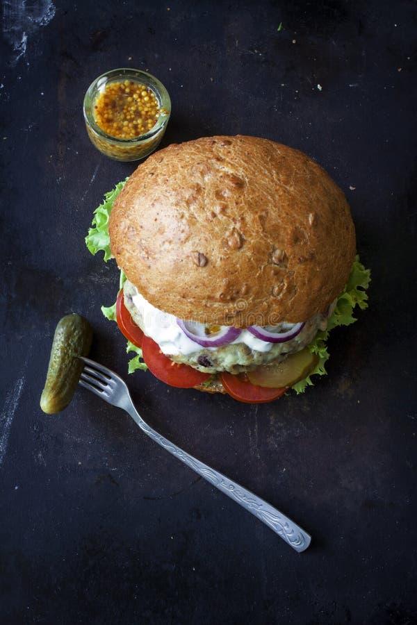 Świeży domowej roboty hamburger z korzennym kumberlandem, cornichons i ziele nad ciemnym metalu tłem, obraz royalty free
