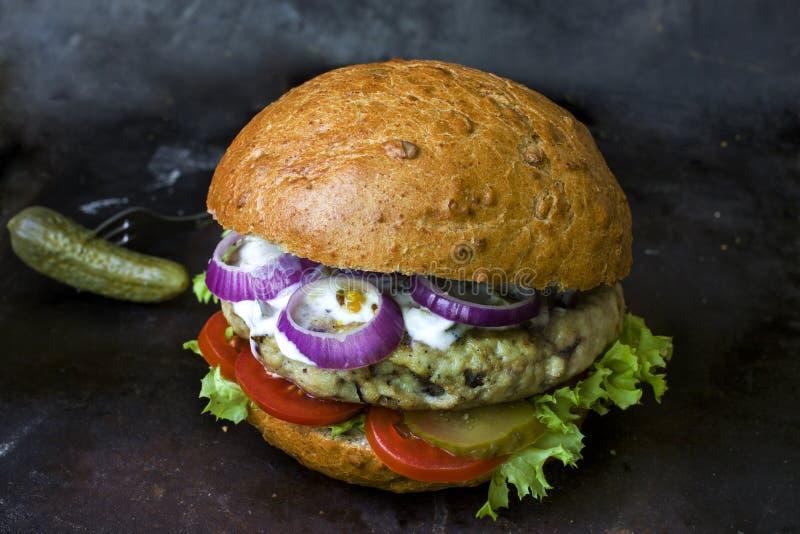 Świeży domowej roboty hamburger z korzennym kumberlandem, cornichons i ziele nad ciemnym metalu tłem, obraz stock