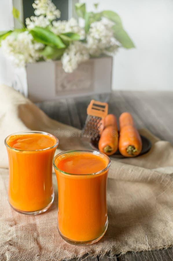 Świeży domowej roboty marchwiany sok w dwa szklanej filiżanki Z marchewką i białymi kwiatami zdjęcia stock