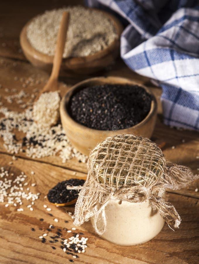 Świeży domowej roboty sezamowy tahini w szklanym słoju i ziarnach w drewnianych pucharach i łyżkach obraz royalty free