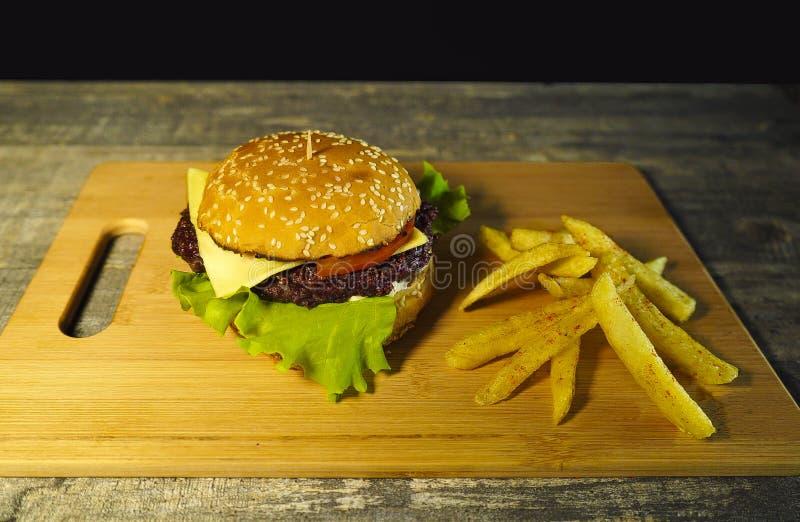 Świeży gorący hamburger na tnącej desce, gotuje obrazy stock