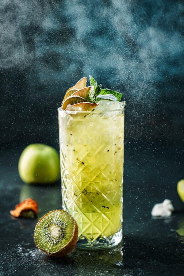 Świeży kiwi koktajl z jabłkiem, mennicą i sproszkowanym cukierem w słoju szkle na zmroku, - błękitny tło Studio strzał napój w mr obrazy stock
