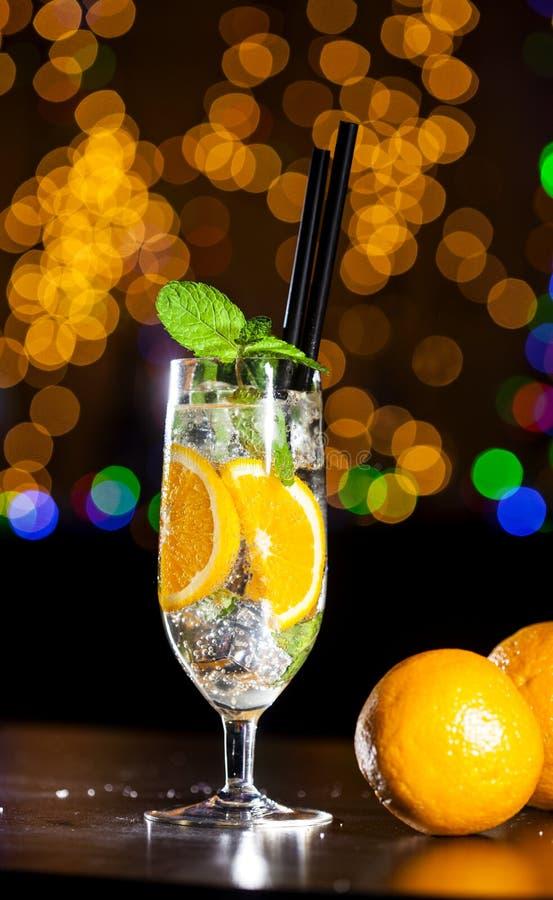 Świeży koktajl z pomarańcze, lodowi ang nowi liście na barze zaświeca tło zdjęcie royalty free
