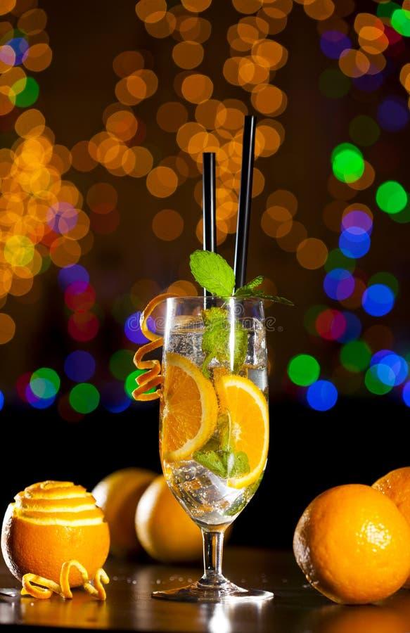 Świeży koktajl z pomarańcze, lodowi ang nowi liście na barze zaświeca tło zdjęcia stock