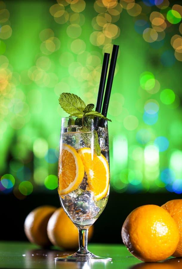 Świeży koktajl z pomarańcze, lodowymi ang nowymi liśćmi na barów światłach i zielonym tłem, obraz royalty free
