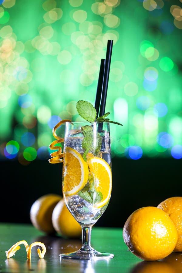 Świeży koktajl z pomarańcze, lodowymi ang nowymi liśćmi na barów światłach i zielonym tłem, obrazy royalty free