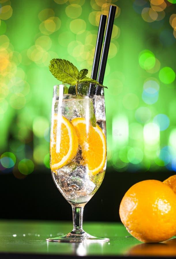 Świeży koktajl z pomarańcze, lodowymi ang nowymi liśćmi na barów światłach i zielonym tłem, fotografia royalty free