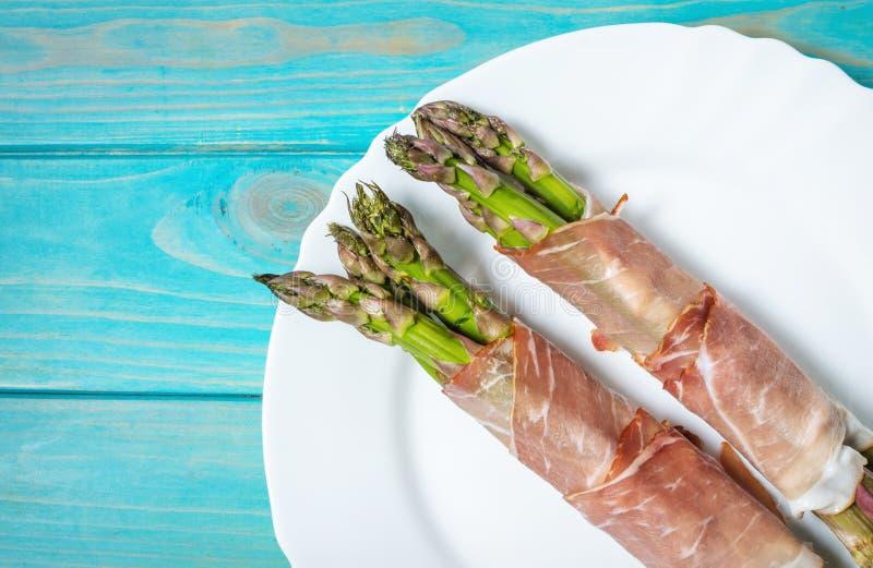 Świeży Młody asparagus Zawijający w Prosciutto mięsie na błękitnym drewno stole zdjęcie royalty free