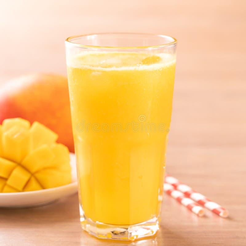 Świeży mangowy sok z pięknymi siekającymi miąższowymi ciałami i słomą na jaskrawym drewnianym stołowym tle Tropikalnej owoc proje obrazy stock