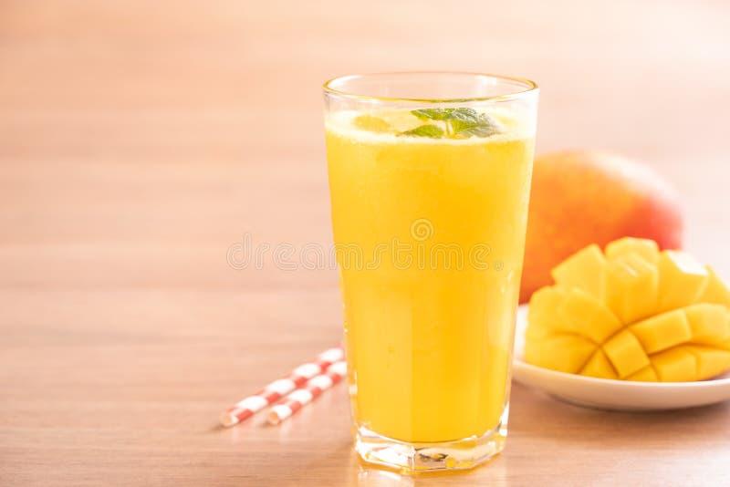 Świeży mangowy sok z pięknymi siekającymi miąższowymi ciałami i słomą na jaskrawym drewnianym stołowym tle Tropikalnej owoc proje zdjęcia royalty free