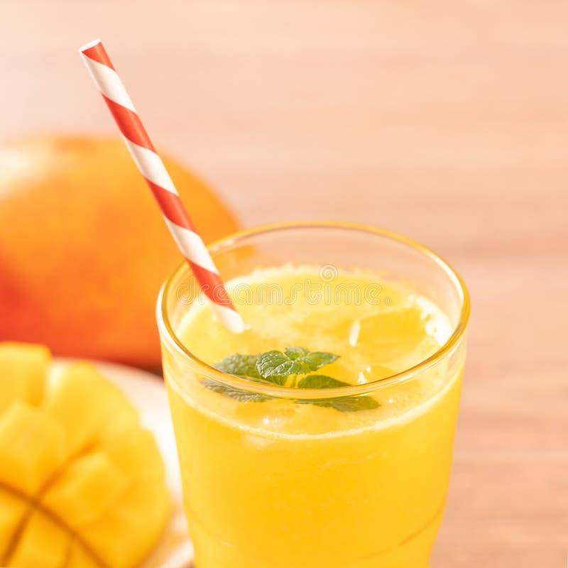 Świeży mangowy sok z pięknymi siekającymi miąższowymi ciałami i słomą na jaskrawym drewnianym stołowym tle Tropikalnej owoc proje fotografia royalty free