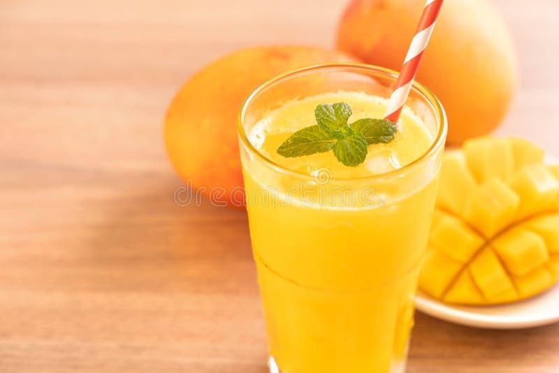 Świeży mangowy sok z pięknymi siekającymi miąższowymi ciałami i słomą na jaskrawym drewnianym stołowym tle Tropikalnej owoc proje zdjęcie royalty free