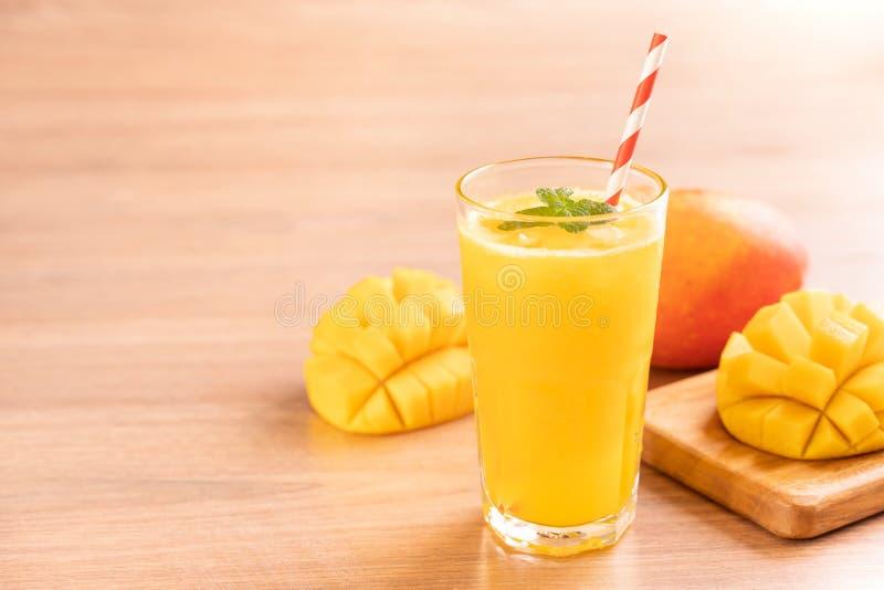 Świeży mangowy sok z pięknymi siekającymi miąższowymi ciałami i słomą na jaskrawym drewnianym stołowym tle Tropikalnej owoc proje zdjęcie stock